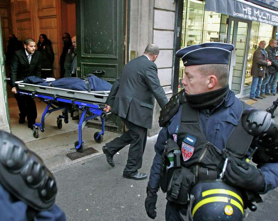 One of the three bodies of the killed Kurdish women is taken out of the building in Paris, Thursday Jan. 10, 2012. Police say three Kurdish women have been shot dead at a pro-Kurdish centre in Paris in what the French interior minister is calling an execution. (AP Photo/Remy de la Mauviniere) Photo: Remy De La Mauviniere