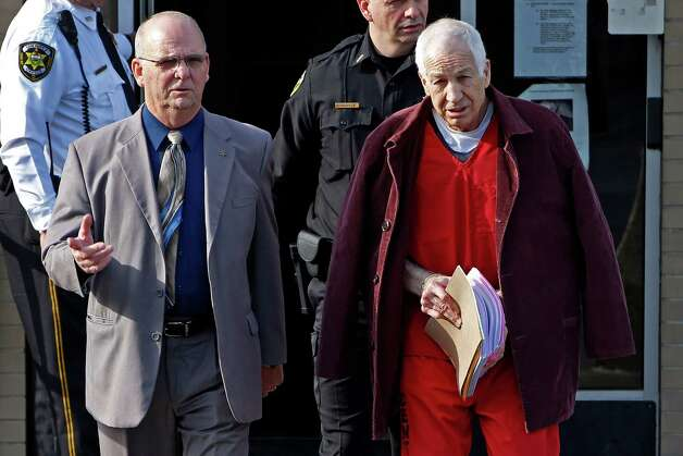 Former Penn State University assistant football coach Jerry Sandusky, left, is essorted by Centre County Sheriff Denny Nau, left, as he leaves the Centre County Courthouse after attending a post-sentence motion hearing in Bellefonte, Pa., Thursday, Jan. 10, 2013. (AP Photo/Gene J. Puskar) Photo: Gene J. Puskar