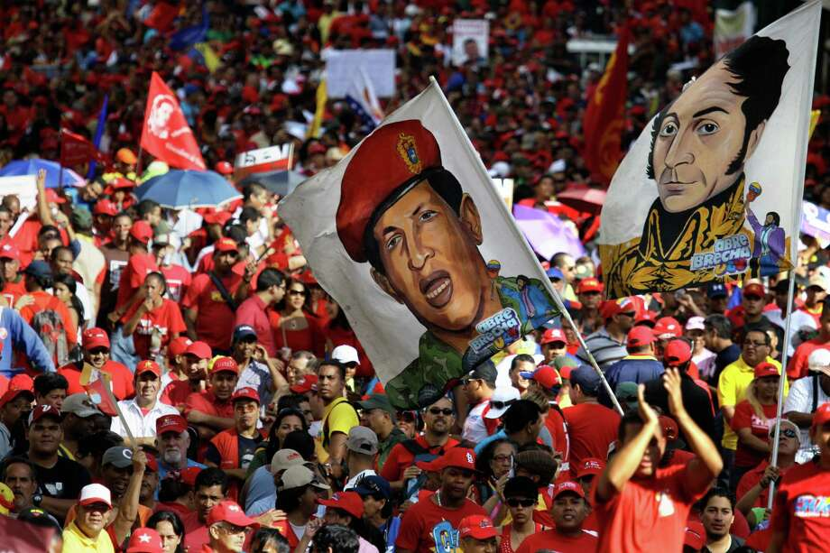 Supporters of Venezuela's President Hugo Chavez wave images of him, second from right, and the Venezuela's independence hero Simon Bolivar during a symbolic inauguration for Chavez outside Miraflores presidential palace in Caracas, Venezuela, Thursday, Jan. 10, 2013. The government organized the unusual show of support for the cancer-stricken leader on the streets outside Miraflores Palace on what was supposed to be his inauguration day. Vice President Nicolas Maduro said that even though it wasn't an official swearing-in, Thursday's event still marks the start of a new term for the president following his re-election in October. (AP Photo/Fernando Llano) Photo: Fernando Llano