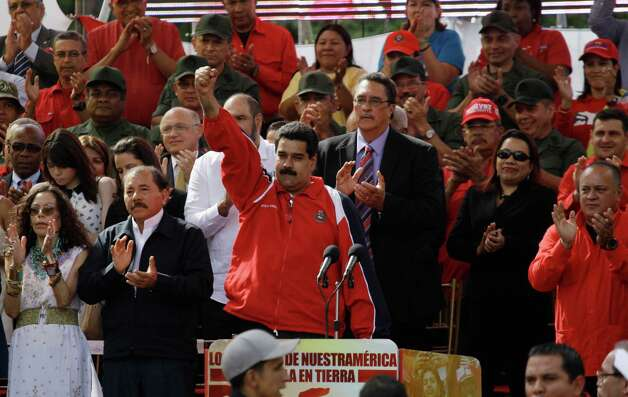 Venezuela's Vice President Nicolas Maduro, center, pumps his fist in the air during a symbolic inauguration for Venezuela's President Hugo Chavez outside Miraflores presidential palace, as National Assembly President Diosdado Caballo, right, looks on in Caracas, Venezuela, Thursday, Jan. 10, 2013.  At left are Nicaragua's President Daniel Ortega and wife Rosario Murillo. The government organized the unusual show of support for the cancer-stricken leader on the streets outside Miraflores Palace on what was supposed to be his inauguration day. Maduro said that even though it wasn't an official swearing-in, Thursday's event still marks the start of a new term for the president following his re-election in October. (AP Photo/Fernando Llano) Photo: Fernando LLano