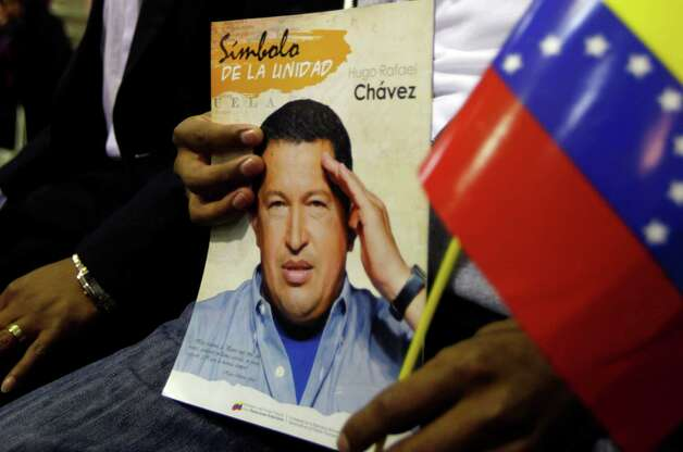 "A man holds a picture of Venezuela's President Hugo Chavez and a Venezuelan flag during a Mass to pray for the leader on what was supposed to be his inauguration day, at a church in La Paz, Bolivia, Thursday, Jan. 10, 2013.  Chavez has been fighting an unspecified type of pelvic cancer since June 2011 and has undergone repeated surgeries, chemotherapy and radiation treatments. Venezuela's government said in its last update on Monday that Chavez was in a ""stable situation"" while being treated for a severe respiratory infection. The government has hasn't said how severe his ""respiratory deficiency"" is. (AP Photo/Juan Karita) Photo: Juan Karita"