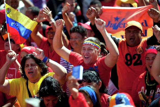 Supporters of Venezuela's President Hugo Chavez chant slogans as they gather for a rally in Caracas, Venezuela, Thursday, Jan. 10, 2013. The government organized the unusual show of support for the cancer-stricken leader on the streets outside Miraflores Palace on what was supposed to be his inauguration day.  Vice President Nicolas Maduro said that even though it wasn't an official swearing-in, Thursday's event still marks the start of a new term for the president following his re-election in October. (AP Photo/Ariana Cubillos) Photo: Ariana Cubillos