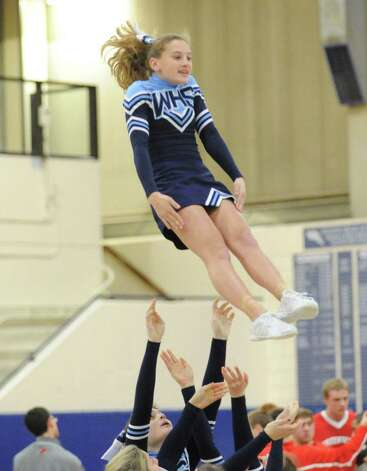 A Wilton cheerleader flies through the air during boys high school basketball game between Wilton High School and Greenwich High School at Wilton, Thursday night, Jan. 10, 2013. Photo: Bob Luckey / Greenwich Time