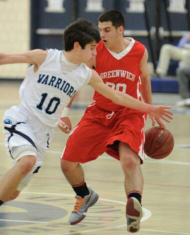 At left, Eric Houska # 10 of Wilton goes for the steal on Jim Djema # 20 of Greenwich during boys high school basketball game between Wilton High School and Greenwich High School at Wilton, Thursday night, Jan. 10, 2013. Photo: Bob Luckey / Greenwich Time