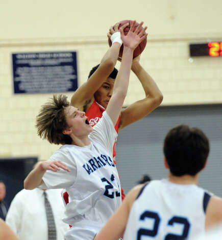 At left, Chris Curtis # 23 of Wilton goes for a rebound against CJ Byrd of Greenwich during boys high school basketball game between Wilton High School and Greenwich High School at Wilton, Thursday night, Jan. 10, 2013. Photo: Bob Luckey / Greenwich Time