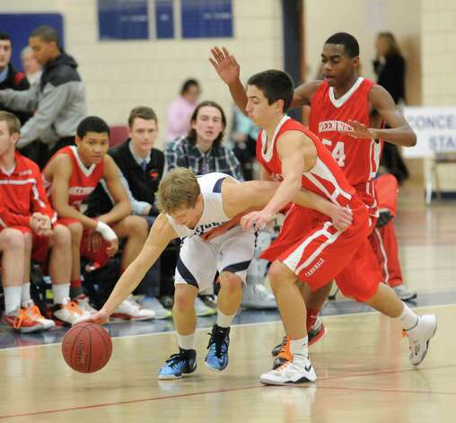 At left, Max Maudsley # 3 of Wilton attempts to dribble out of a double coverage siutation by Greenwich during boys high school basketball game between Wilton High School and Greenwich High School at Wilton, Thursday night, Jan. 10, 2013. Photo: Bob Luckey / Greenwich Time