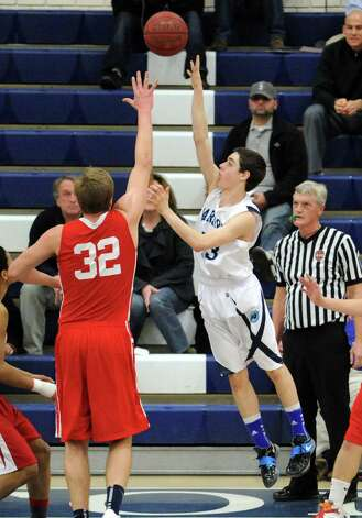At left, Alex Wolf of Greenwich goes for a block on Matt Shifrin of Wilton during boys high school basketball game between Wilton High School and Greenwich High School at Wilton, Thursday night, Jan. 10, 2013. Photo: Bob Luckey / Greenwich Time