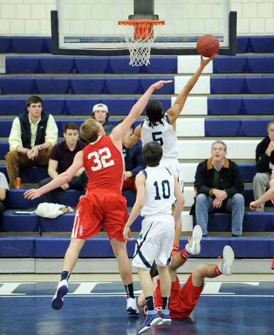 At left, Alex Wolf # 32 of Greenwich goes to block the shot of Olondi LeGrand # 5 of Wilton during the boys  high school basketball game between Wilton High School and Greenwich High School at Wilton, Thursday night, Jan. 10, 2013. Photo: Bob Luckey / Greenwich Time