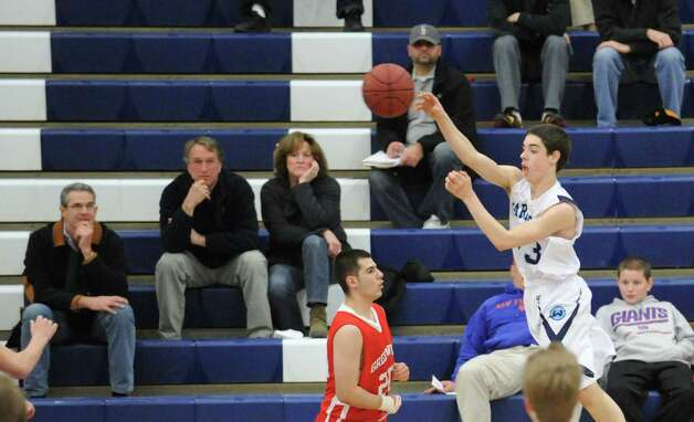 At right, Matt Shifrin of Wilton passes the ball while being covered by Jim Djema of Greenwich during boys high school basketball game between Wilton High School and Greenwich High School at Wilton, Thursday night, Jan. 10, 2013. Photo: Bob Luckey / Greenwich Time