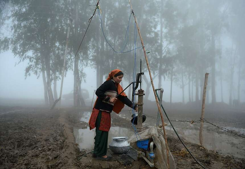An Indian woman uses a hand pump to  during a dense fog along the India-Pakistan border in Suchit-Ga