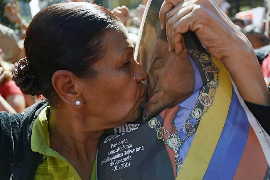 A woman kisses a portrait of Venezuelan President Hugo Chavez during a meeting outside Miraflores Presidential Palace in Caracas on January 10, 2013. With Chavez ailing and absent, Venezuela's leftist government launches a new presidential term with a display of popular support on the day he was to be inaugurated. The Supreme Court cleared the cancer-stricken president to indefinitely postpone his re-inauguration and said his existing administration could remain in office until he is well enough to take the oath. Photo: Leo Ramirez, AFP/Getty Images