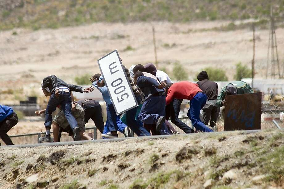 Striking farmworkers try to hide from police behind broken road signs during violent clashes, on January 10, 2012 in de Doorns, a small farming town about 140Km North of Cape Town, South Africa. The farm workers have said that they they will not return to work on the fruit growing region's farms until they receive a daily wage of at least R150($17) per day, which is about double what they currently earn. Photo: Rodger Bosch, AFP/Getty Images