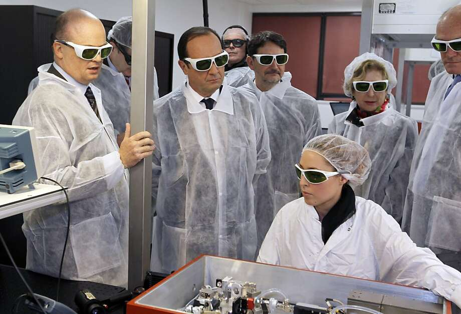 French President Francois Hollande wearing security glasses looks at a technician at work as he visits the Amplitude Systemes plant, specialized in ultrafast diode-pumped solid-state lasers, in Pessac near Bordeaux, in southwestern France, on January 10, 2013. Photo: Regis Duvignau, AFP/Getty Images