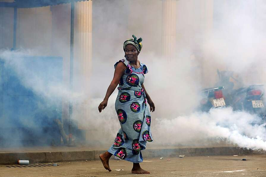A woman runs as police shoot teargas at protesters during the first of a three-day planned demonstra