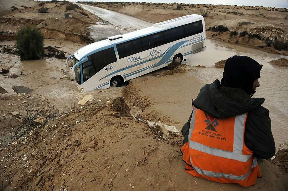 A man sits in front of a bus that was swept off the road by flooding due to heavy rainfall in the southern Israeli Negev Desert on January 10, 2013. The worst storms in a decade left swathes of Israel and Jordan under a blanket of snow and parts of Lebanon blacked out, bringing misery to a region accustomed to temperate climates. Photo: David Buimovitch, AFP/Getty Images