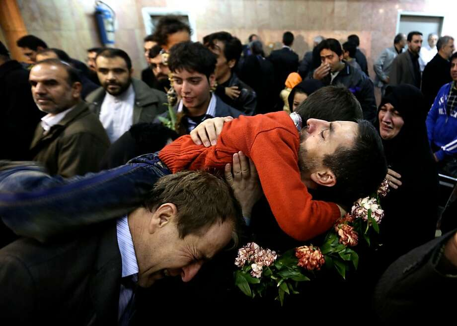 Reza Sohrabi, an Iranian man who has been held hostage, alongside 48 other Iranians, by Syrian rebels since early August 2012, hugs his son after arriving at Tehran's Mehrabad airport on January 10, 2013. The rebels agreed to swap the 48 Iranians, described by the Islamic republic as pilgrims but by the rebels and Washington as members of Iran's elite Revolutionary Guards, for more than 2,000 detainees held by the Syrian regime. Photo: Behrouz Mehri, AFP/Getty Images