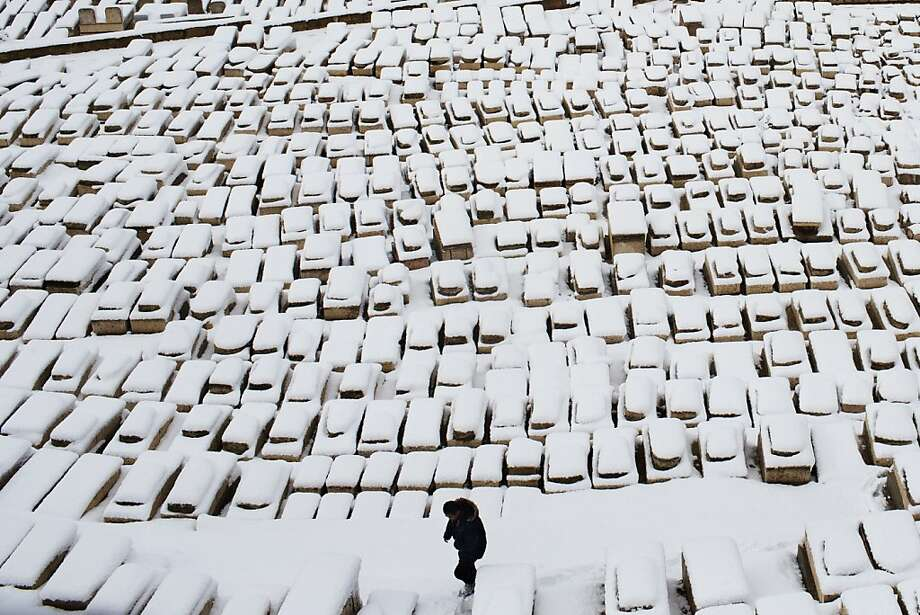 A man walks through tombs covered by snow on the Mount of Olives, in Jerusalem, Thursday, Jan. 10, 2013. Stormy weather conditions continued on Thursday with snow, torrential rains and strong winds across the region. Photo: Bernat Armangue, Associated Press