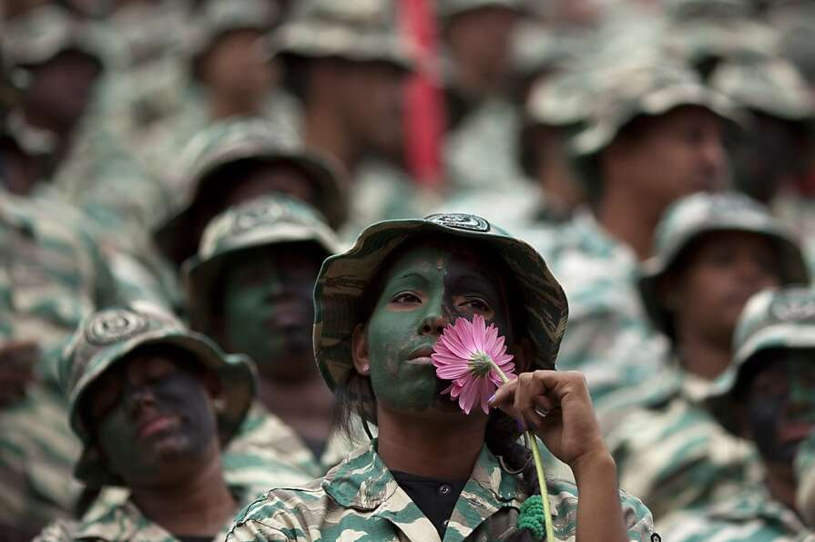 A female member of Venezuela's Bolivarian militia, in uniform with her face painted, holds a flower