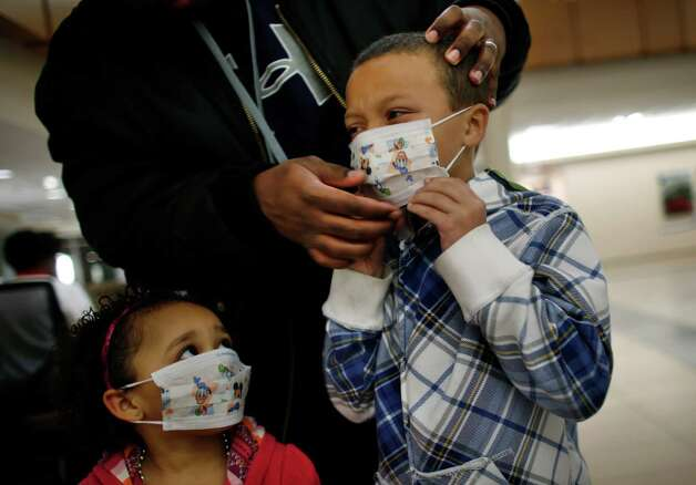 Here Damien Dancy puts masks on his children Damaya, 3, left, and Damien, 7, on Wednesday, Jan. 9, 2013 at Sentara Princess Anne Hospital in Virginia Beach, Va.   Hospitals in Hampton Roads are urging patients and visitors to wear a mask at their facilities to help stop the spread of the flu. The recommendation was issued Wednesday by more than two dozen medical centers. In a joint statement, the hospitals said the recommendation applies to hospitals, urgent care centers and branch clinics, among others. (AP Photo/The Virginian-Pilot, Stephen M. Katz) Photo: Stephen M. Katz