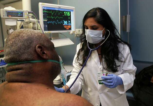 Dr. Meeta Khan wears a face mask as she examines a respiratory patient at the Rush University Hospital emergency department, Thursday, Jan. 10, 2013, in Chicago. Flu season in the U.S. has hit early and, in some places, hard. But whether this will be considered a bad season by the time it has run its course in the spring remains to be seen. (AP Photo/Charles Rex Arbogast) Photo: Charles Rex Arbogast