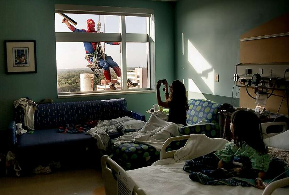 Sao Doan, 5, right, watches as  her mom, Tiffany Ringer, both of Kenneth City, snaps a photo of Merrill Hunt dressed as  Spiderman  as he washes her window at All Children's Hospital Thursday morning Jan. 10, 2013. Three window cleaners dressed as Spider-Man from High Rise Window Cleaning Company started cleaning windows on the outside of All ChildrenÍs Hospital Thursday morning. Photo: Cherie Diez, Associated Press