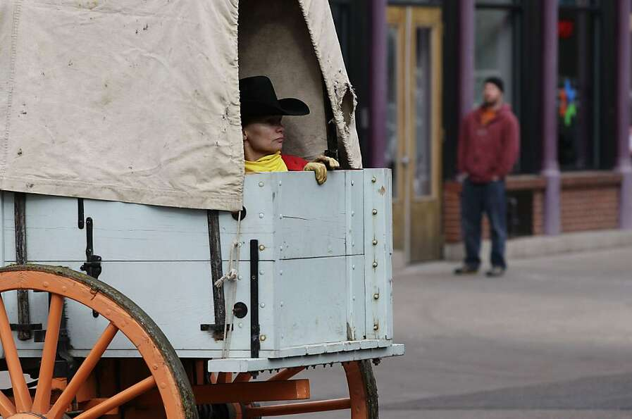 A woman rides inside a covered wagon during the annual parade kicking off the National Western Stock
