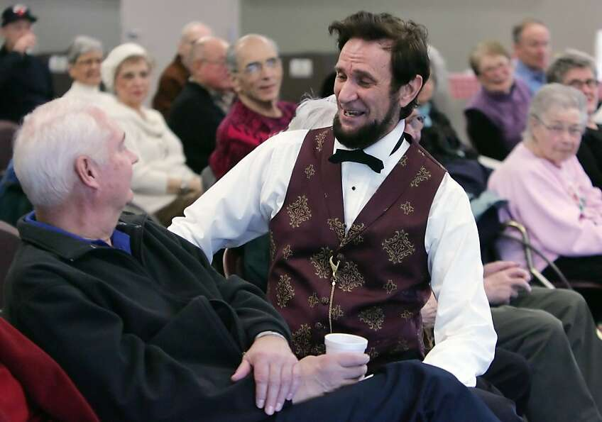 President Abraham Lincoln, played by Michael Krebs, sits in the audience and talks to Howard Koster,