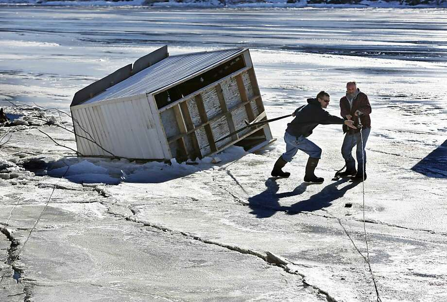 Brett McKenna, left, helps Randy Kensell attach a tow line to Kensell's ice fishing shack  Thursday, Jan. 10, 2013, on the Kennebec, River in Pittston, Maine. The shack was unoccupied when strong winds toppled the shack and blew onto soft ice. The shack was eventually hauled to land, saving Kensell from a possible fine of up to $1,000.  Photo: Robert F. Bukaty, Associated Press