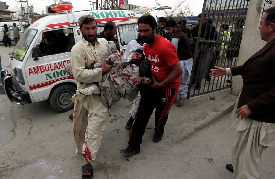 Pakistani volunteers rush an injured victim from a bomb blast to a local hospital for treatment in Quetta, Pakistan, Thursday, Jan. 10, 2013. A bomb targeting paramilitary soldiers killed scores of people in southwest Pakistan, officials said. (AP Photo/Arshad Butt) Photo: Arshad Butt