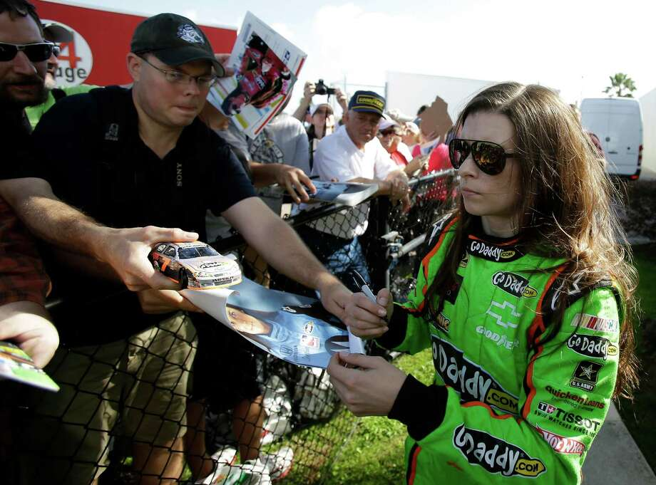 Driver Danica Patrick, right, signs autographs for fans after the morning session of NASCAR auto race testing at Daytona International Speedway, Thursday, Jan. 10, 2013, in Daytona Beach, Fla. (AP Photo/John Raoux) Photo: John Raoux