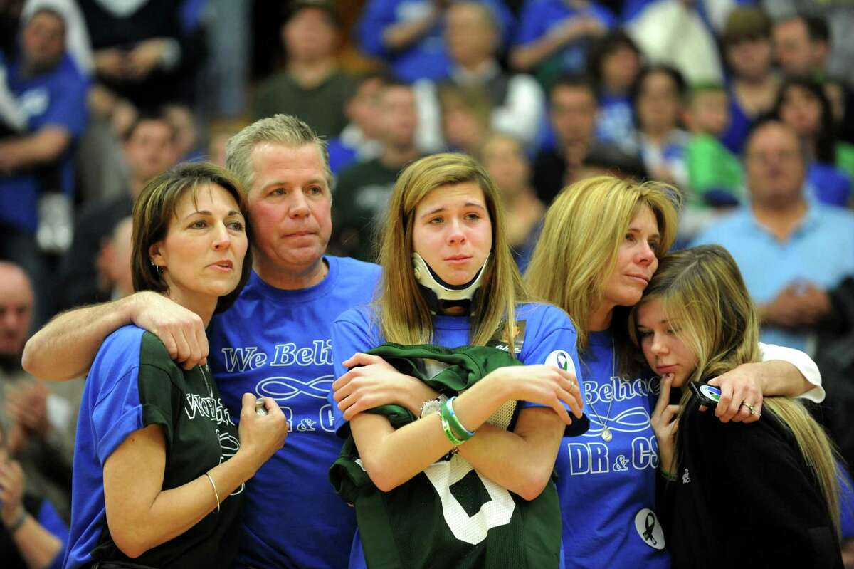 Bailey Wind, 17, center, hugs a jersey with the number 69, worn by her late-boyfriend Chris Stewart, during a ceremony on Thursday, Jan. 10, 2013, at Siena College in Loudenville, N.Y. Joining her, from left, are Regina Stewart, Bobby Wind, Dawn Wind and Nikki Wind, 15. Shaker and Shenendehowa girls and boys basketball teams played games to benefit the memorial scholarship funds for Shenendehowa athletes Chris Stewart and Deanna Rivers, who were both killed in a recent car crash. Their jersey numbers were retired. (Cindy Schultz / Times Union)