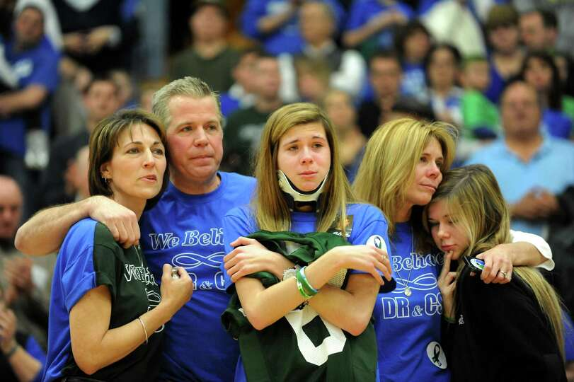 Bailey Wind, 17, center, hugs a jersey with the number 69, worn by her late-boyfriend Chris Stewart,
