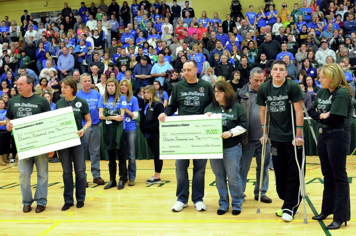 The parents of Chris Stewart, left, and Deanna Rivers, center, hold checks during a ceremony on Thursday, Jan. 10, 2013, at Siena College in Loudenville, N.Y. Shaker and Shenendehowa girls and boys basketball teams played games to benefit the memorial scholarship funds for the two athletes, who were both killed in a recent car crash. (Cindy Schultz / Times Union)