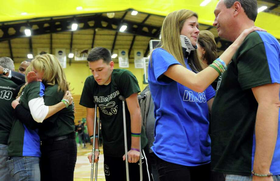 Mike Stewart, right, Bailey Wind, second from right, and Matt Hardy, are among the friends and family greeting each other during a ceremony on Thursday, Jan. 10, 2013, at Siena College in Loudenville, N.Y. Shaker and Shenendehowa girls and boys basketball teams played games to benefit the memorial scholarship funds for Chris Stewart and Deanna Rivers, who were both killed in a recent car crash. (Cindy Schultz / Times Union) Photo: Cindy Schultz / 00020711A