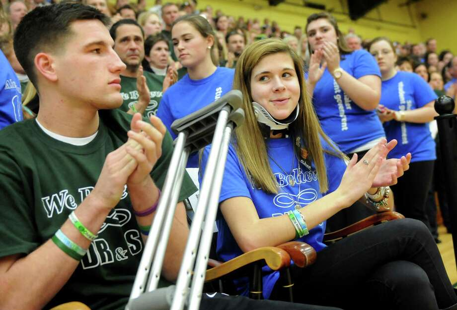 Bailey Wind, 17, center, and Matt Hardy, 17, applaud at introductions during a ceremony on Thursday, Jan. 10, 2013, at Siena College in Loudenville, N.Y. Shaker and Shenendehowa girls and boys basketball teams played games to benefit the memorial scholarship funds for Chris Stewart and Deanna Rivers, Shenendehowa athletes who were both killed in a recent car crash. (Cindy Schultz / Times Union) Photo: Cindy Schultz / 00020711A