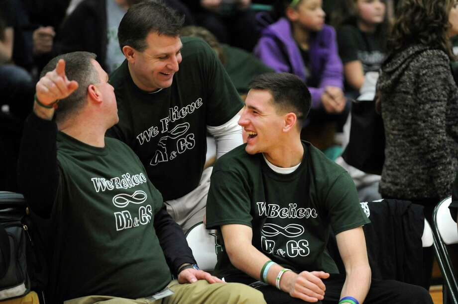 Crash survivor Matt Hardy, 17, right, sits on the Shenendehowa bench and jokes with athletic director Chris Culnan, center, and athletic trainer Rick Knizek on Thursday, Jan. 10, 2013, at Siena College in Loudenville, N.Y. Shaker and Shenendehowa girls and boys basketball teams played games to benefit the memorial scholarship funds for Chris Stewart and Deanna Rivers, Shenendehowa athletes who were both killed in a recent car crash. (Cindy Schultz / Times Union) Photo: Cindy Schultz / 00020711A