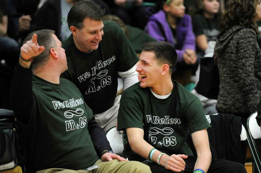 Crash survivor Matt Hardy, 17, right, sits on the Shenendehowa bench and jokes with athletic directo