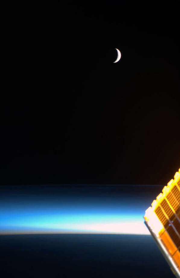 Hadfield says this photo shows the moon at sunrise, with ethereal blue noctilucent clouds and a solar array glowing gold.