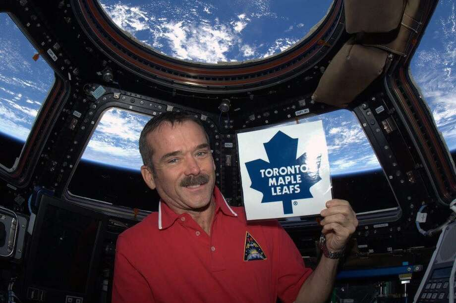 Hadfield holds a sign showing his support for the Toronto Maple Leafs after the end of the NHL lockout Jan. 6. Photo: Cmd. Chris Hadfield, Associated Press / The Canadian Press via NASA,Chri
