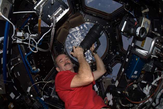 Hadfield is shown in the Cupola of the International Space Station with a camera. He told followers the Space Station uses Nikon D2 and D3 cameras with several different lenses.