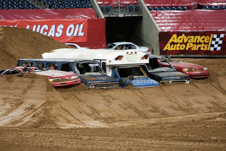 Vehicles are seen covered with dirt along the track in preparation for Advance Auto Parts Monster Jam, Friday, Jan. 11, 2013, in Houston. Approximately 12 feet tall and about 12 feet wide, monster trucks are custom-designed machines that sit atop 66-inch-tall tires and weigh a minimum of 10,000 pounds. Built for short, high-powered bursts of speed, monster trucks generate 1,500 to 2,000 horsepower and are capable of speeds of up to 100 miles per hour. Monster trucks can fly up to125 to 130 feet (a distance greater than 14 cars side by side) and up to 35 feet in the air. Photo: Cody Duty, Houston Chronicle / © 2012 Houston Chronicle