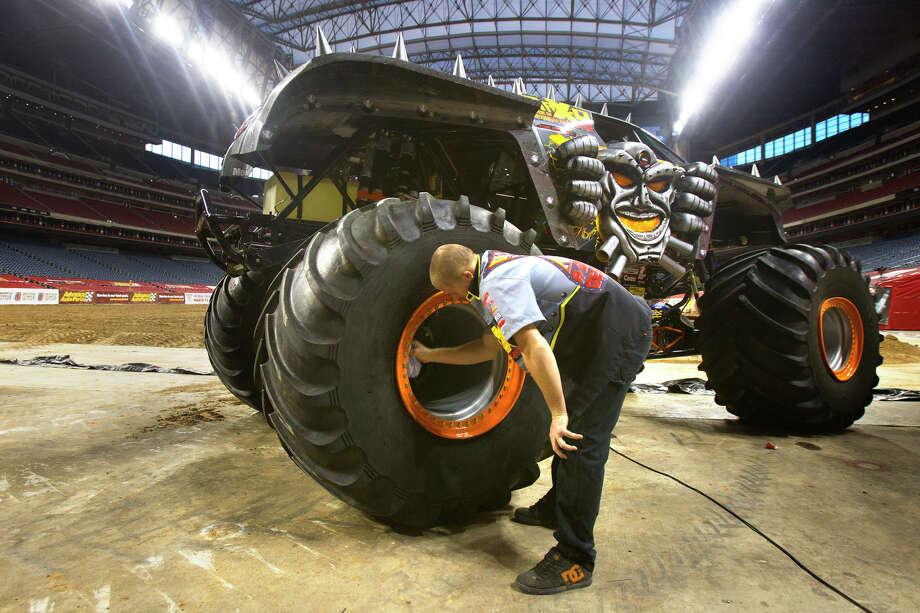Trey Hart cleans the wheels of the Max-D truck in preparation for Advance Auto Parts Monster Jam, Friday, Jan. 11, 2013, in Houston. Approximately 12 feet tall and about 12 feet wide, monster trucks are custom-designed machines that sit atop 66-inch-tall tires and weigh a minimum of 10,000 pounds. Built for short, high-powered bursts of speed, monster trucks generate 1,500 to 2,000 horsepower and are capable of speeds of up to 100 miles per hour. Monster trucks can fly up to125 to 130 feet (a distance greater than 14 cars side by side) and up to 35 feet in the air. Photo: Cody Duty, Houston Chronicle / © 2012 Houston Chronicle