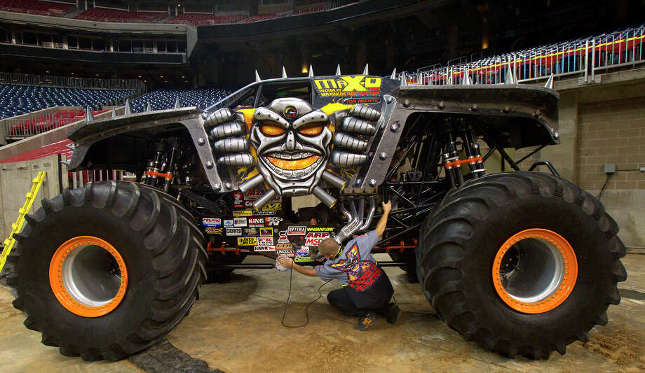 Trey Hart runs a rag over the Max-D truck in preparation for Advance Auto Parts Monster Jam, Friday, Jan. 11, 2013, in Houston. Approximately 12 feet tall and about 12 feet wide, monster trucks are custom-designed machines that sit atop 66-inch-tall tires and weigh a minimum of 10,000 pounds. Built for short, high-powered bursts of speed, monster trucks generate 1,500 to 2,000 horsepower and are capable of speeds of up to 100 miles per hour. Monster trucks can fly up to125 to 130 feet (a distance greater than 14 cars side by side) and up to 35 feet in the air. Photo: Cody Duty, Houston Chronicle / © 2012 Houston Chronicle