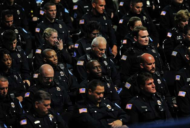 Beaumont Police officers listen to a song played during the funeral services for officer Bryan Hebert at the Civic Center on Wednesday. Hebert was killed in the line of duty on Friday. Guiseppe Barranco/The Enterprise