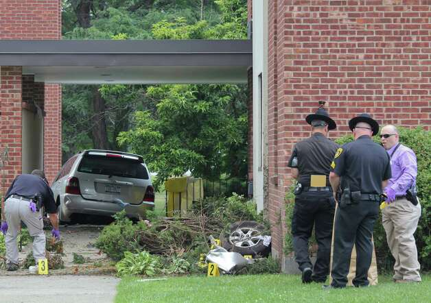 Law enforcement officers investigate a crash site at St. Matthew's church on Mountain View Street  Wednesday, Aug. 10, 2011, in Voorheesville, N.Y. The accident resulted in the deaths of three people. The front tire of the SUV was ripped from the car when it struck the corner of the church. (Erin Colligan /Times Union archive)