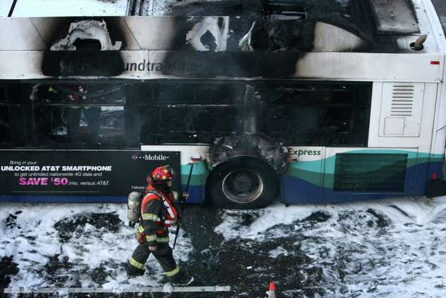 Firefighters work the scene after a Sound Transit express bus erupted in flames on Friday, January 11, 2013 on the southbound Interstate 5 express lanes. Photo: JOSHUA TRUJILLO / SEATTLEPI.COM