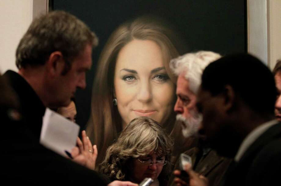 Members of the media talk to artist Paul Emsley, center right, in front of his newly-commissioned portrait of Kate, Duchess of Cambridge, on display at the National Portrait Gallery in London, Friday, Jan. 11, 2013. (AP Photo/Sang Tan) Photo: Sang Tan