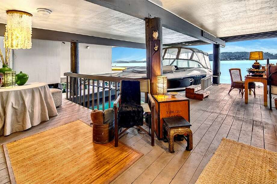 Dock-level entertaining area of 9860 Rainier Ave. S. The 2,601-square-foot house, built in 1971, has four bedrooms, two bathrooms, exposed wood beams, a sauna, decks, views and a two-car garage on a 1,213-square-foot lot with 50 feet of frontage along Lake Washington. It's listed for $650,000. Photo: Courtesy Bryan Loveless And Richard Eastern/Windermere Real Estate