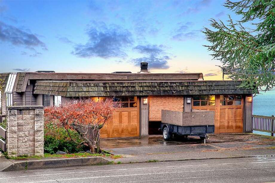 Two-car garage of 9860 Rainier Ave. S. The 2,601-square-foot house, built in 1971, has four bedrooms, two bathrooms, exposed wood beams, a covered, dock-level entertaining area, a sauna, decks and views on a 1,213-square-foot lot with 50 feet of frontage along Lake Washington. It's listed for $650,000. Photo: Courtesy Bryan Loveless And Richard Eastern/Windermere Real Estate