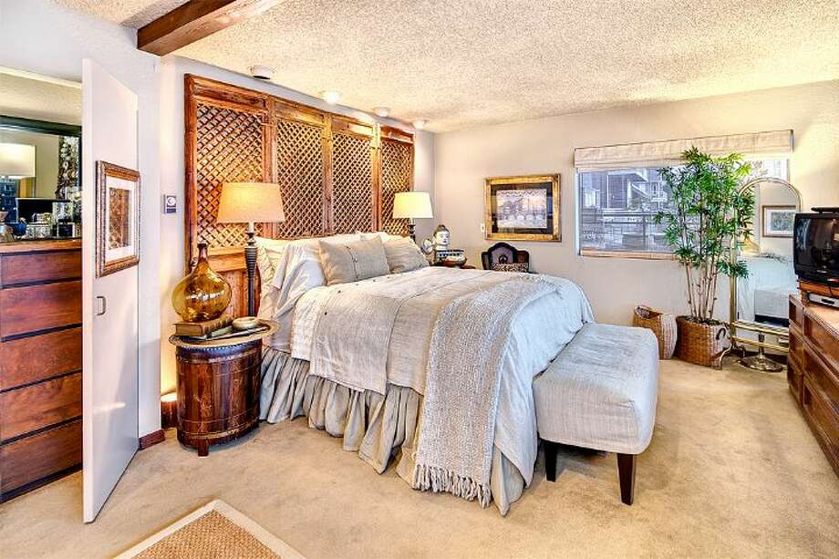 Master bedroom of 9860 Rainier Ave. S. The 2,601-square-foot house, built in 1971, has four bedrooms, two bathrooms, exposed wood beams, a covered, dock-level entertaining area, a sauna, decks, views and a two-car garage on a 1,213-square-foot lot with 50 feet of frontage along Lake Washington. It's listed for $650,000. Photo: Courtesy Bryan Loveless And Richard Eastern/Windermere Real Estate